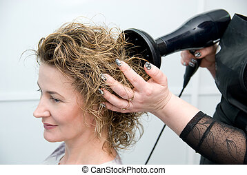 stylist drying woman hair