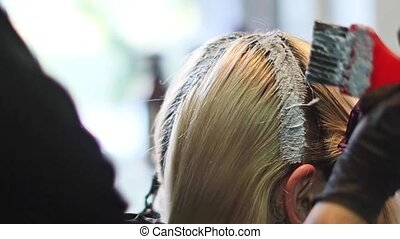 Stylist hairdresser makes hair coloring, blonding, coloring...