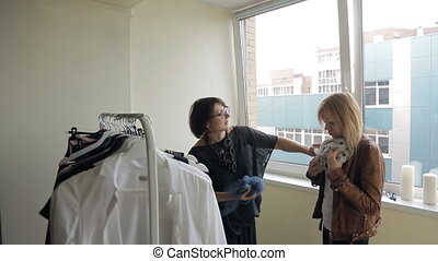 Stylist helps client to choose scarf which suits her jacket better. Blond in brown leather jacket wants something to add her look. First she tries white scarf with black peas. Brunette puts aside blue variant shows how lady can tie this accessory. Consultant demonstrates length of neckerchief and ...
