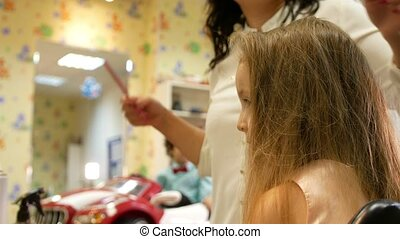 Stylist is curling and cumbing long hair for little cute...