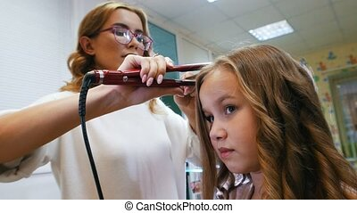 Stylist is curling long hair for little cute girl, using...