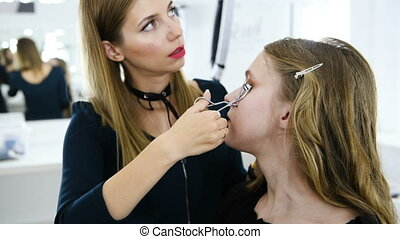 Stylist is forming eyelashes using curler for young girl -...