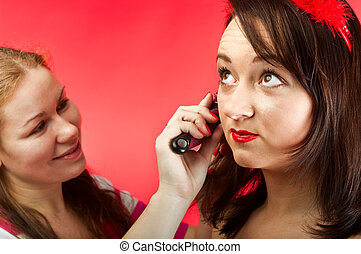 Stylist make image of contemporary model in photographic studio. Two young women. Facial portrait.