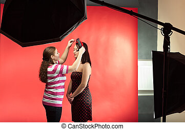 Stylist make image of contemporary model in photographic studio. Two young women. Photo equipment