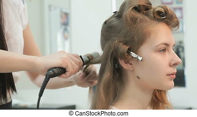Stylist makes curls brown-haired using a curling - Stylist...