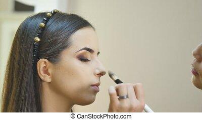 Stylist makes professional eye makeup. Beautiful model. -...