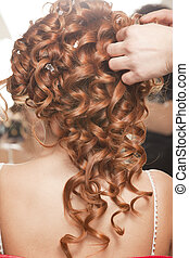 bride - Stylist pinning up a bride's hairstyle before the ...