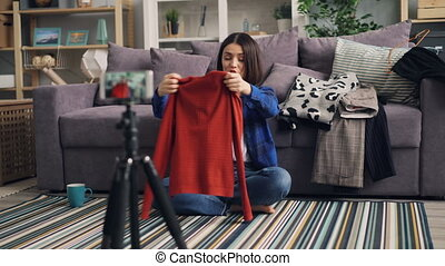 Stylist recording video about clothing holding jumper using...