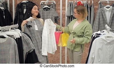 Stylist selects a set of casual clothes to women in a store at shopping mall.