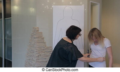 Stylist shows figure features for client outline full-length sketch.