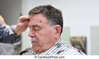 Stylist sprays hair of senior man with water. Professional stylist makes modern haircut for senior man in barbershop. Hairdresser sprays male hair with water .