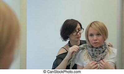 Stylist ties beautiful white blue scarf to client in fashion shop.