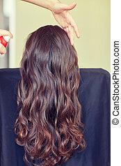 stylist with hair spray making hairdo at salon - beauty, ...