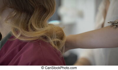 Stylist with her hands smoothes long hair on the woman's back.