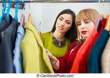 stylist working with wardrobe - girl with stylist choosing...