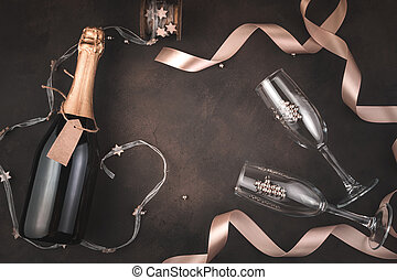 Stylized Christmas background with a bottle of champagne and wine glasses on a brown background.