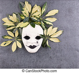 Stylized mask and tropical palm leaves on gray background.