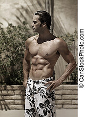 Stylized portrait of a beautiful muscular wet male model outdoors in swim trunks