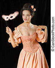 Stylized rococo portrait of beautiful brunette woman in historical costume with crinoline and mask. Low key