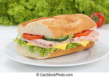 Sub sandwich baguette on plate with ham, cheese, tomatoes and lettuce for breakfast