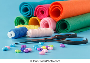Subjects for sewing clothes. Spool of thread, scissors, ribbons, a set of needles, buttons need for tailoring and needlework.