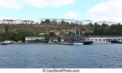 submarine and the warship on the anchor parking in a bay of...