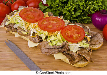 Fresh and tasty submarine sandwich on a wooden plank, vegetables in background.