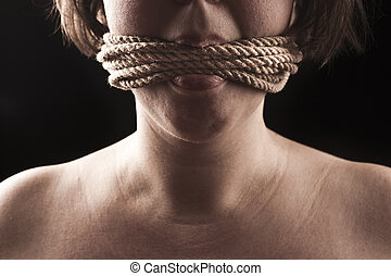 submissive girl gagged with rope on a black background