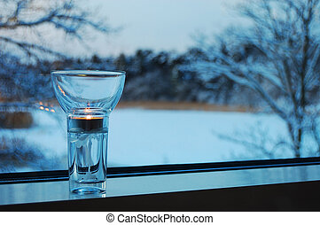 Subtle candle on a window-sill with winter forest at the ...