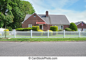 Suburban Brick Home white picket fence American Flag