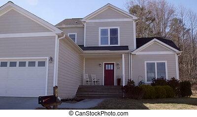 Suburban house white and tan establishing shot with mailbox...