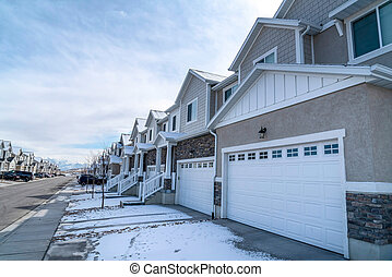 Suburban neighborhood with road along snowy driveways of townhouses in winter