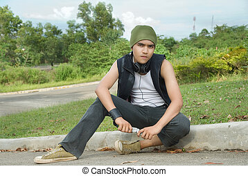 Suburban rapper sitting on street