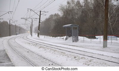 Suburban train arriving at the station, snowstorm, slow...