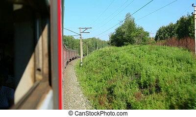 Suburban train crosses the forest in the Novosibirsk region