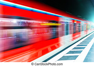 Subway metro train at railway station platform with motion blur