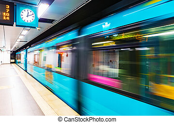Subway metro train at railway station platform with motion blur