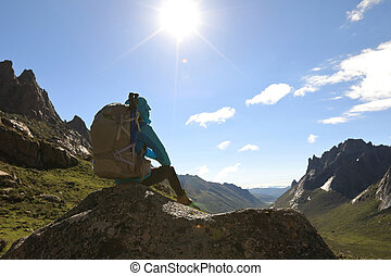 succesful woman with backpack hiking in mountains