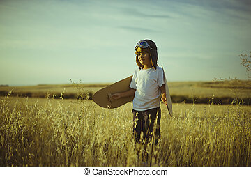 Success, Boy playing to be airplane pilot, funny guy with aviator cap and glasses, carries wings made of brown cardboard as an airplane