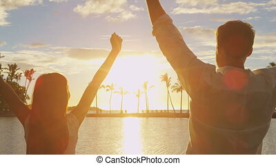 Success, celebrating concept with people cheering of joy bliss at beach sunset on at beautiful sunset on beach. Couple on travel vacation having fun in amazing light.