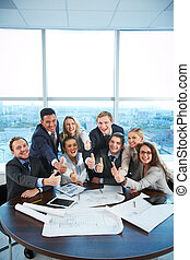 Success in business - Group of business partners sitting at...