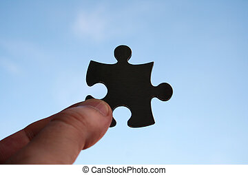 Success - Jigsaw pice on human fingers against the sky