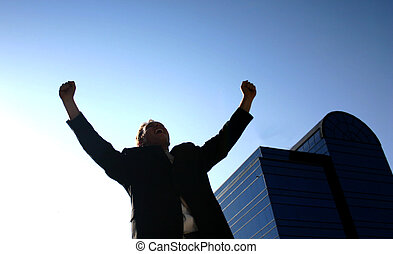 man raises his arms in front of building