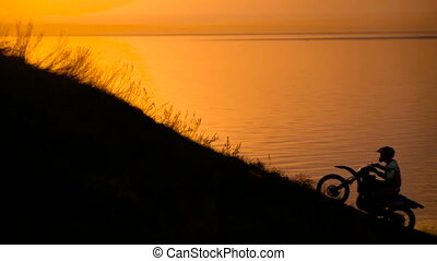 success. motocross bike at sunset on hill climbs. Extreme...
