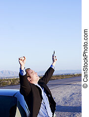 Success on the road - man raises his hands while celebrating