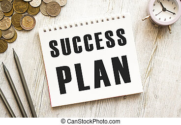 SUCCESS PLAN text on a sheet of notepad. Coins are scattered, pencils on a gray wooden background.