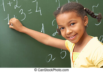 Portrait of smart schoolchild standing at blackboard and looking at camera