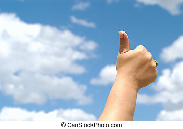 thumbs up againsts a bright blue sky.