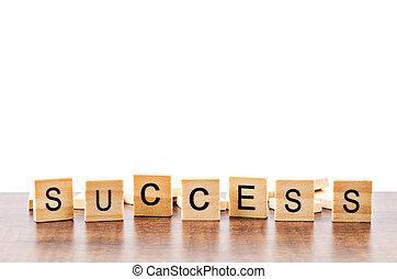 Success word wood on table.