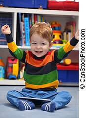 Successful 2 years old boy winning using a digital tablet computer